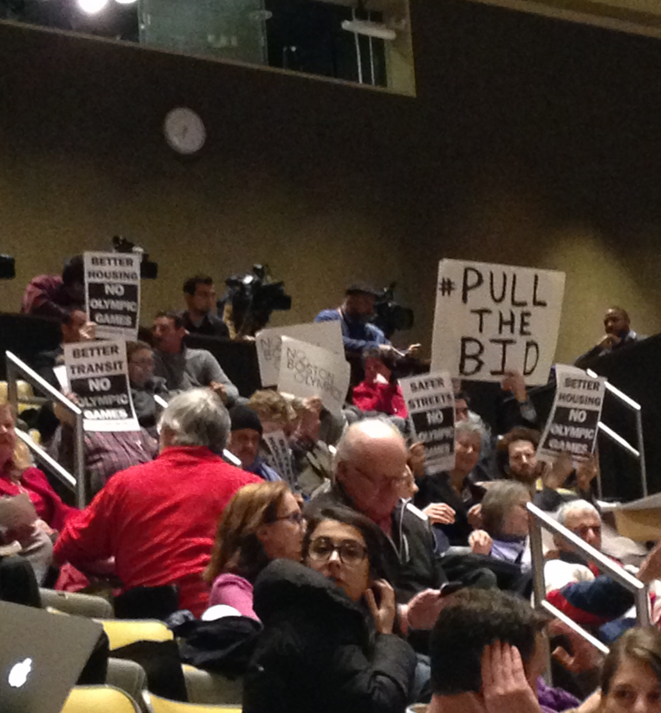 A protestor holds up a #PulltheBid sign at a Boston2024 community meeting